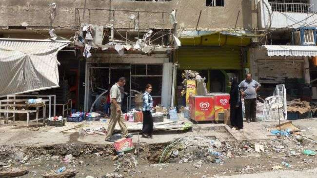 Iraqis inspect the damage outside shops in Baghdad on June 25, 2013 following an explosion the night before.
