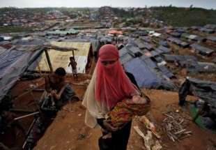 A Rohingya refugee carries her child in a refugee camp in Cox
