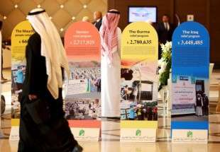 Participants walk past brochures of previous funds collected by the International Islamic Relief Organization (IIRO), during the Kuwait International Conference for Reconstruction of Iraq