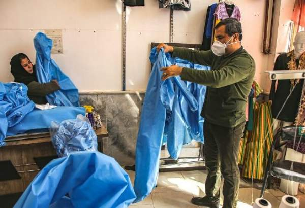 An Iranian tailor checks a hospital gown as different NGOs, state organizations and sections have begun nation-wide battle against coronavirus.