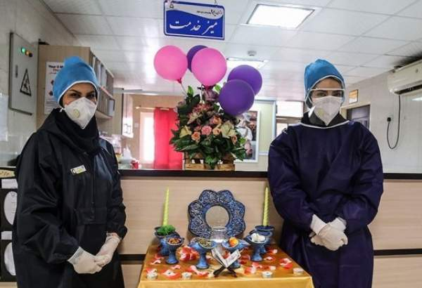Two Iranian nurses in coronavirus-infection ward, standing next to Haft Seen set, traditional set of items laid to mark beginning of the Persian New Year as the country is challenged by COVID-19 on the eve of the New Year 1399. (Photo: Tasnim)