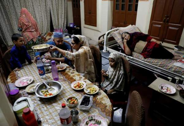 Gohar Sultan, 70, looks on as her family eats an Iftar meal at their house, in the old quarters of Delhi, India, April 25, 2020.