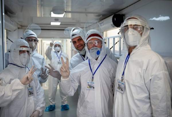 A group of Iranian nurses in hospital gowns and protective face masks pose for a photo.
