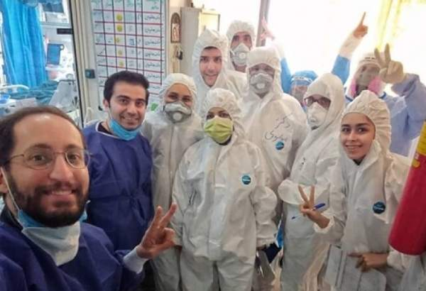 A group of Iranian in hospital gowns and protective gears against the new coronavirus pose for a photo.