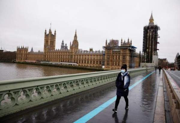 A woman wearing a face mask walks across Westminster Bridge past the Houses of Parliament in London, Britain, December 22, 2020 as the news over new variant of COVID-19 shakes the British nation and world people.